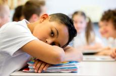 Young male student resting head on desk